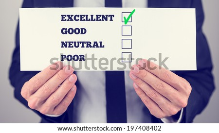 Businessman in a suit holding a survey check with multiple choice check boxes for excellent - good - neutral - poor ratings with a green check mark in excellent. - stock photo
