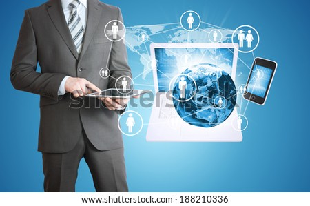 Businessman in a suit holding a tablet. Near the earth and electronics. Elements of this image are furnished by NASA