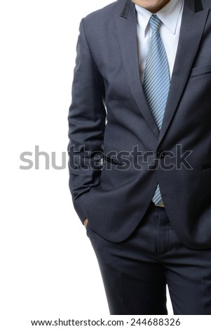 businessman in a suit holds hands in pockets isolated on white background - stock photo