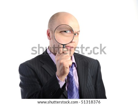 Businessman in a suit looking through a magnifying glass. Isolated on white background