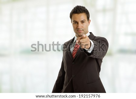 businessman in a suit pointing with his finger at the office - stock photo