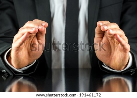 Businessman in a suit sitting at a desk making a protective gesture with his cupped hands reflected in the shiny surface below with space for your product placement. - stock photo