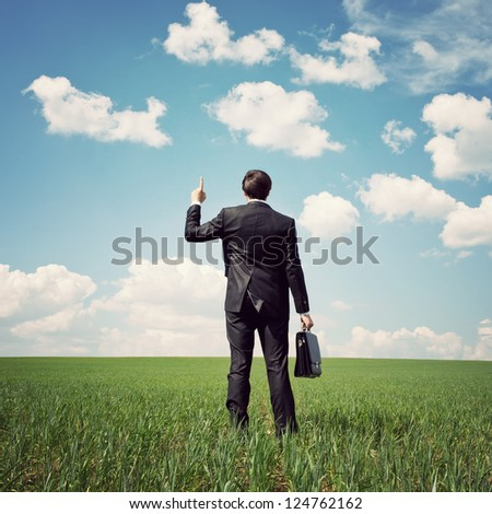 businessman in a suit standing in the field and points a finger at something - stock photo