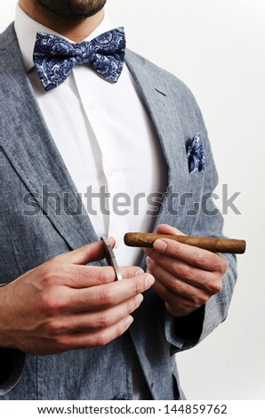 Businessman in a suit with blue handkerchief and bow tie cutting cigare - stock photo