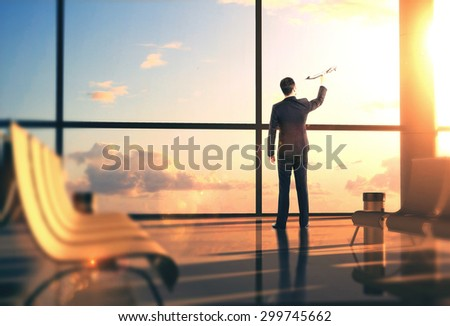 businessman in airport with airplane in hand - stock photo