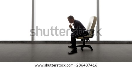 Businessman in an empty office for a startup business or a failed entrepreneur with an empty office due to bankruptcy.  The lonely mood is set by the back light from the windows