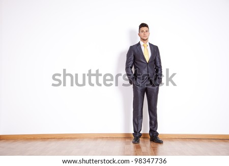 businessman in an empty room next to the wall - stock photo