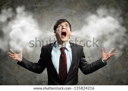 businessman in anger screaming puff going out from ears - stock photo