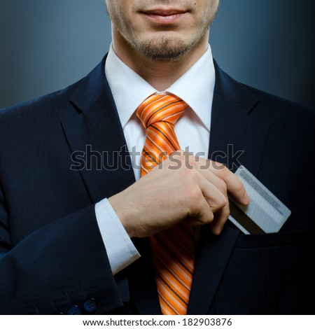businessman in black costume and orange necktie put or take out credit card in pocket - stock photo