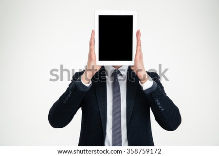 Businessman in black suit and white shirt holding blank screen tablet in front of his head over white background - stock photo