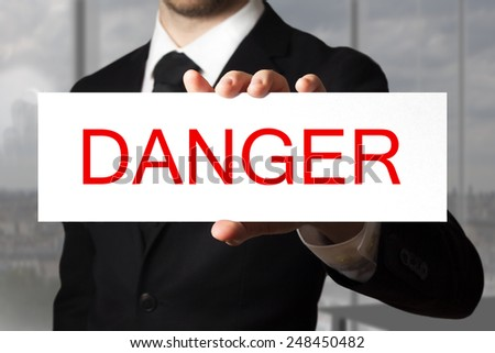 businessman in black suit holding sign danger - stock photo