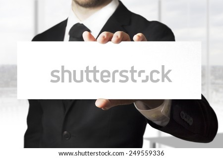 businessman in black suit holding sign empty - stock photo