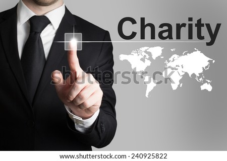 businessman in black suit pushing touchscreen button charity world - stock photo