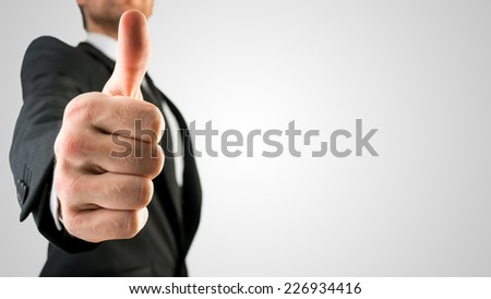 Businessman in Black Suit Showing Thumbs Up Sign, Emphasizing Approval or Satisfaction, in Close Up. Isolated on Gray Background. - stock photo