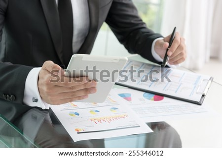 businessman in black suit use tablet and read report in office - stock photo