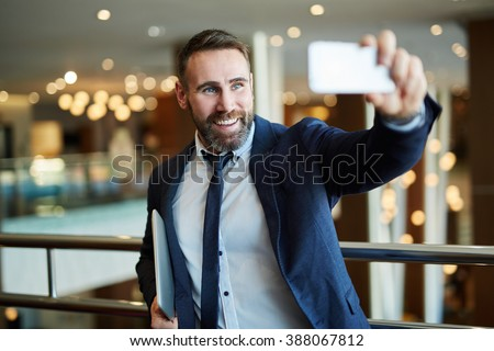 Businessman in black suit using a mobile phone for a video call with partners - stock photo