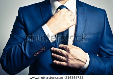 Businessman in blue suit tying the necktie - stock photo