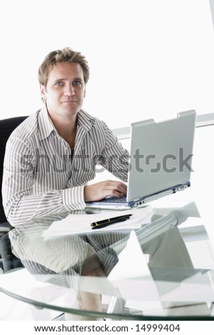 Businessman in boardroom with laptop - stock photo