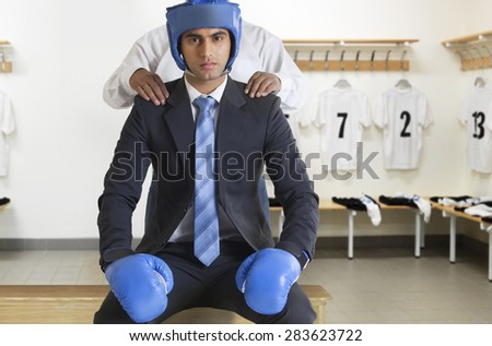 Businessman in boxing gear getting a massage - stock photo