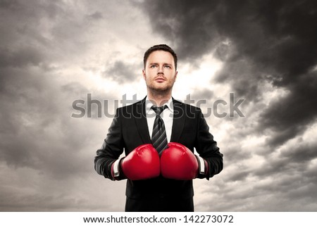 businessman in boxing gloves on cloud background - stock photo