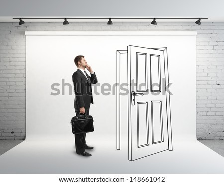 businessman in brick room with drawing door