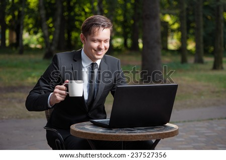 Businessman in cafe. Attractive young caucasian businessman in formalwear working on laptop and smiling while sitting and holding cup of coffee in sidewalk cafe - stock photo