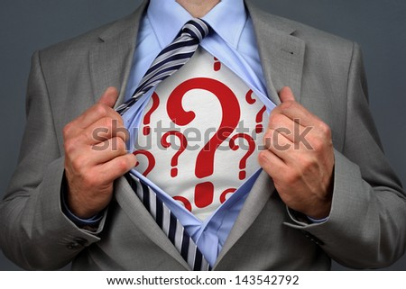 Businessman in classic superman pose tearing his shirt open to reveal question mark symbol on chest concept for human resources and recruitment - stock photo