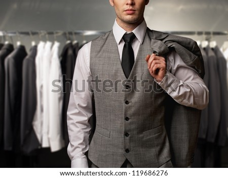 Businessman in classic vest against row of suits in shop - stock photo