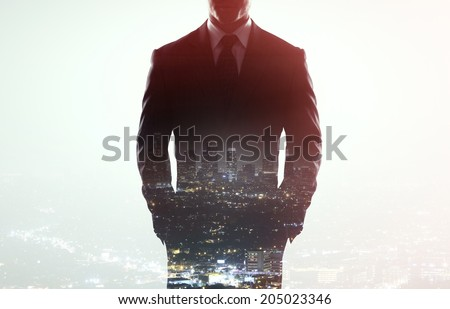 businessman in coat on a city background - stock photo