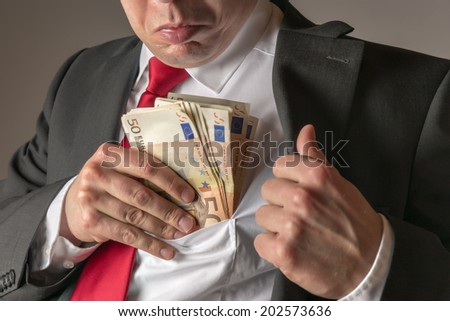 Businessman in dark suit and with tie putting money in his pocket - stock photo
