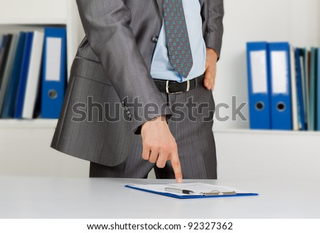 Businessman in elegant suits working with documents sign up contract sitting at the desk at office - stock photo