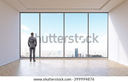 Businessman in empty office with panoramic window. Back view. City and sky view. Concept of new office. - stock photo
