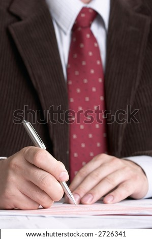 Businessman in formal clothing signing the document, close-up.
