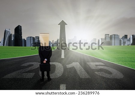Businessman in formal suit with cardboard head standing on the highway turning into arrow upward toward the future of 2015 - stock photo