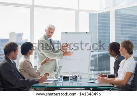 Businessman in front of a growing chart during a meeting with concentrated colleagues - stock photo
