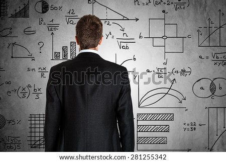Businessman in front of math formulas - stock photo