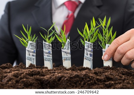 Businessman In Front Of New Plant Covered With American Dollar - stock photo