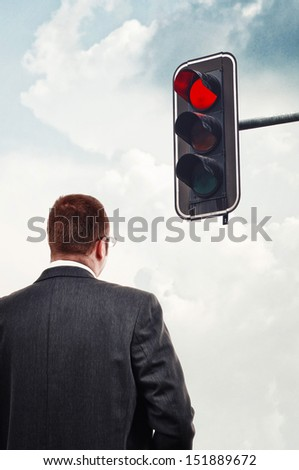 Businessman in front of red traffic light. Business obstacles concept.