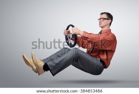 Businessman in glasses car driver with a steering wheel - stock photo