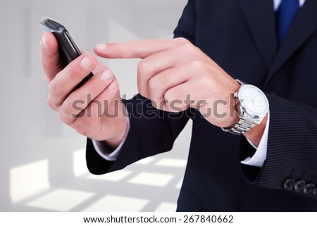 Businessman in glasses using his tablet pc against white room with squares at wall