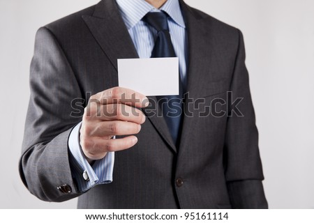Businessman in grey suit and a blue shirt with a blue tie, shows business card with copy space, shallow dept of field, isolated on a grey background - stock photo
