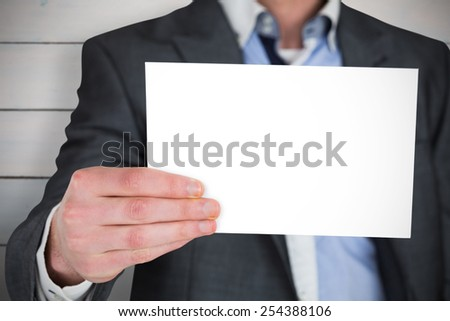 Businessman in grey suit showing card against painted blue wooden planks - stock photo