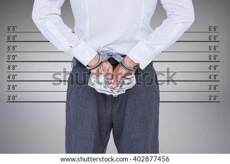Businessman in handcuffs holding bribe against digitally generated image of height measurement - stock photo