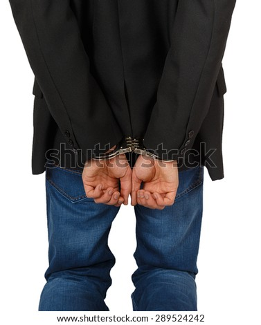 Businessman in handcuffs standing isolated on white background - stock photo