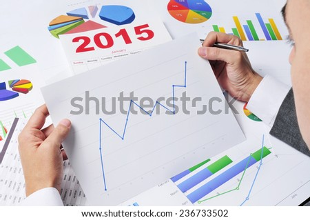 businessman in his office desk observing a chart with an upward trend, with a 2015 calendar in the background - stock photo