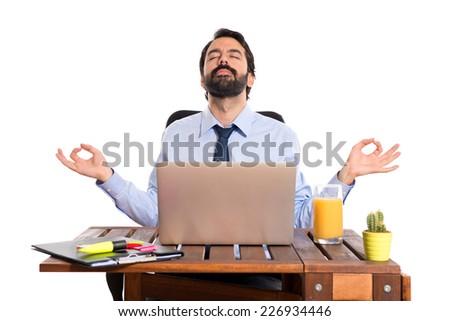 Businessman in his office  in zen position - stock photo