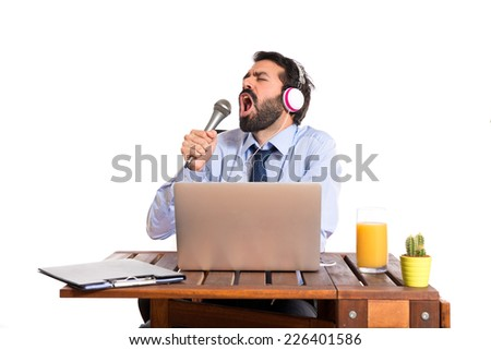 Businessman in his office singing - stock photo