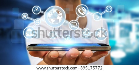 Businessman in his office using a digital web network with his mobile phone - stock photo