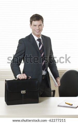 Businessman in his office with briefcase