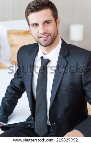 Businessman in hotel room. Confident young businessman in formalwear looking at camera and smiling while sitting on the bed in hotel room  - stock photo